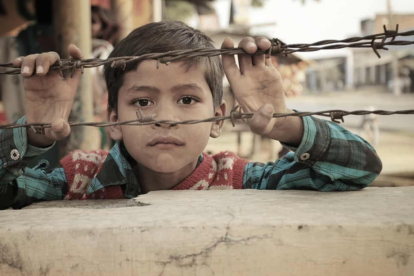 An Indian Child looking into barbwire fence